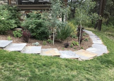 flagstone walkway with a landscaped garden